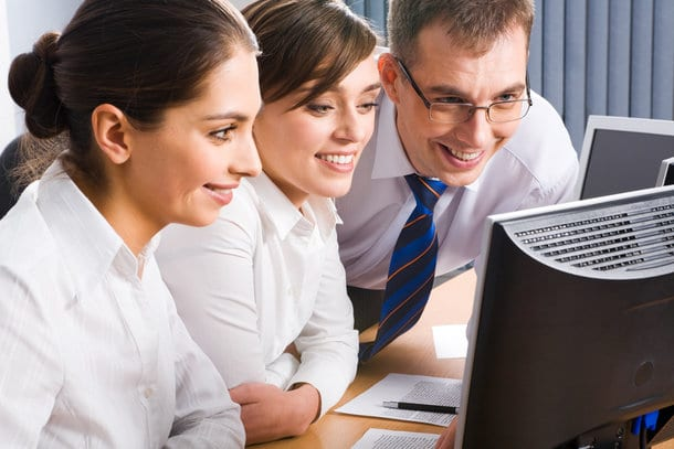 Team of three business people looking at the monitor